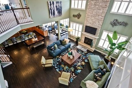 dramatic two story great room with a stacked stone fireplace creates