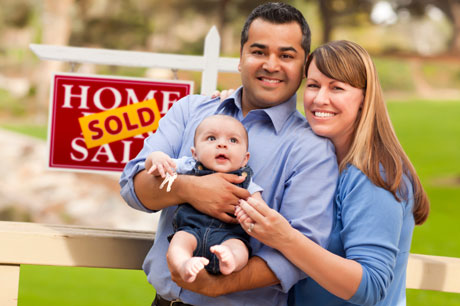 Multicultural Couple with Sold Sign