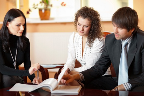 Couple with Agent Reviewing Paperwork