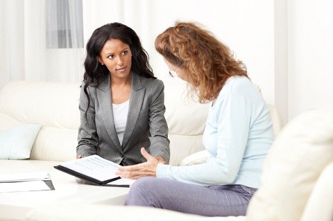 Woman Sitting With Realtor Going Over Papaerwork