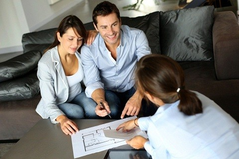 Couple with agent looking at a floor plan
